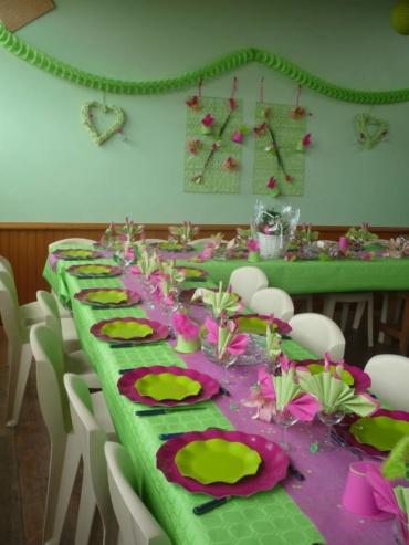 décoration de table thème majorette avec nappe de couleur verte, chemin de table rose fushia brillant, de petits chapeaux de majorettes en carton et bâtons de majorette décorés
