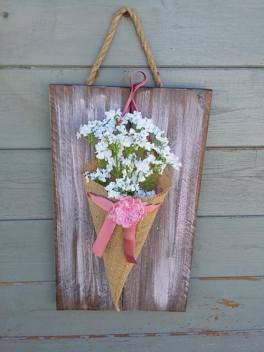 cône de fleurs en toile de jute avec une fleur en tissus posé sur sur un noeud en satin rose et le tout fixé sur un cadre en bois teinté et légèrement patiné rose tendre.