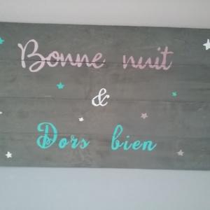 cadre en bois de palette pour chambre d'enfant peint en gris avec inscriptions aux couleurs douces