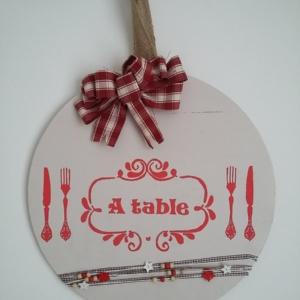 décor de porte en bois rond peint de couleur crème, gros noeud rouge et blanc, inscriptions rouge, le tout tenu par un ruban en toile de jute