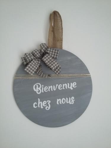 décor de porte en bois rond peint en couleur gris et une très légère patine blanche, un gros noeud Vichy gris, inscription blanche, le tout tenu par un ruban en toile de jute.