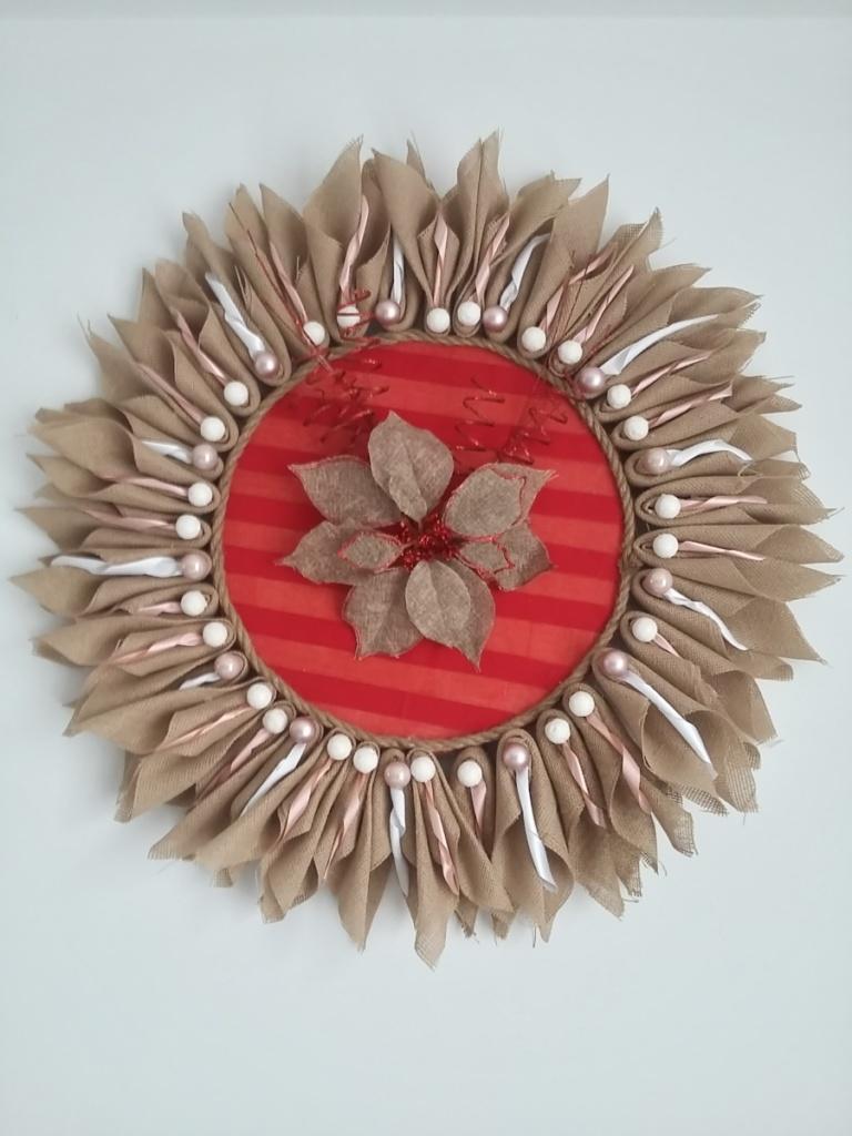 grande couronne de noël en toile de jute en forme de soleil avec au milieu de la toile de jute couleur rouge, une fleur en toile de jute naturel et fils torsadés rouge pailletés. La couronne fait 80 cm de diamètre