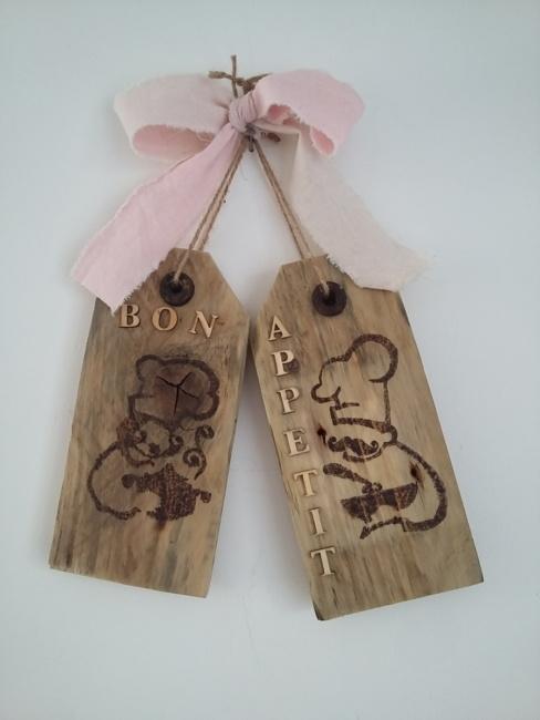 plaque de porte en bois brut pour la cuisine avec 2 dessins pyrogravés, les mots bon appétit en lettres en bois naturel, le tout tenu par une corde et un gros noeud en lin rose