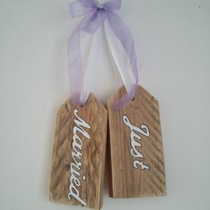 plaque de porte en bois brut avec inscriptions just married, le tout tenu par un ruban de satin blanc et un gros noeud en ruban de satin mauve transparent