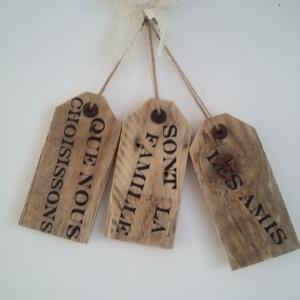plaque de porte en bois brut avec les inscriptions les amis sont la famille que nous choisissons en noire, le tout tenu par une cordelette et un noeud en dentelle crème