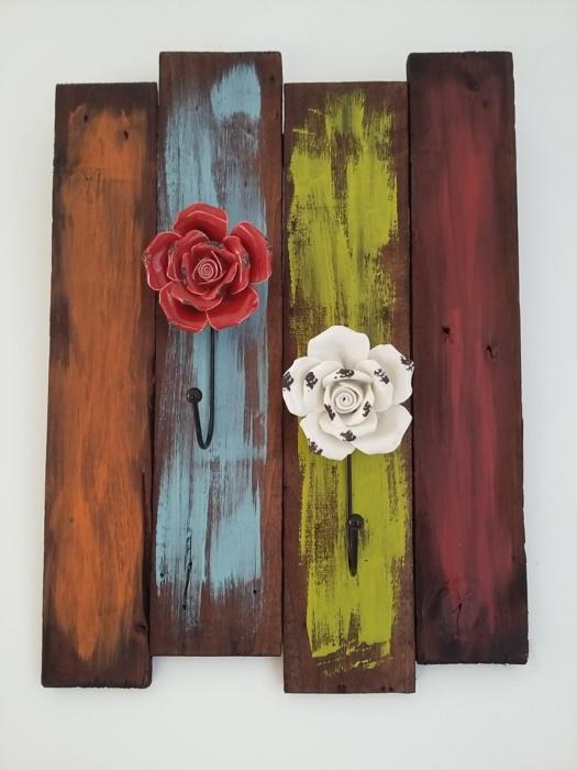 porte serviettes en bois teinté foncé et coups de peinture pour un effet peps avec patères en forme de fleurs en porcelaine de couleur rouge et blanche