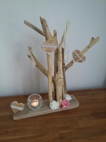 bougeoir posé sur une planche de bois avec du bois flotté agrémenté de coeurs en bois chantourné et de dentelle