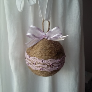 Grosse boule de noël fait avec de la ficelle de lin, des bouts de dentelle rose collés tout autour, des petits strass et un gros noeuds en satin rose transparent