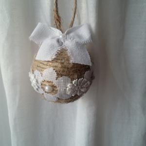 Petite boule de noël fait avec de la ficelle de lin, des bouts de dentelle blanche collés tout autour, des petits strass et un noeud en lin blanc