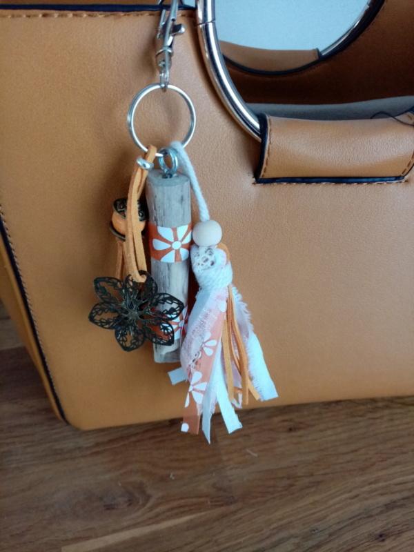 Bijoux de sac en bois flotté avec perles, ornement et pompons en tissus couleur orangé.