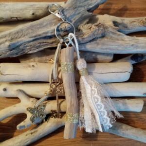 Bijoux de sac avec bois flotté, perles, ornement et pompon tissus, couleur or.