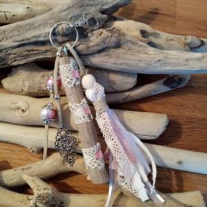 Bijoux de sac avec bois flotté, dentelle, perles, ornement et pompon en tissus couleur rose.
