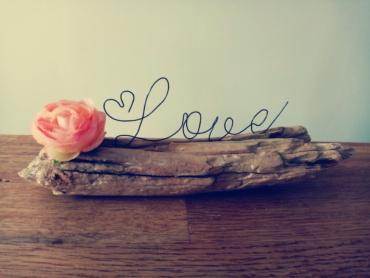 Ecriture en fil de fer, le mot love, posé sur du bois flotté