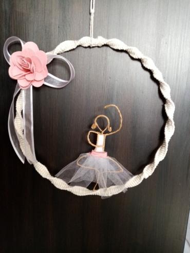 Petite danseuse étoile en fil de kraft armé, posée délicatement sur son cercle en macramé.