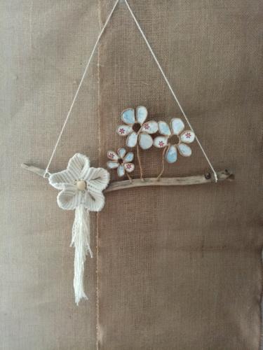 Suspension avec une fleur en macramé et trois fleurs en fil de kraft armé, posées délicatement sur une branche de bois flotté.