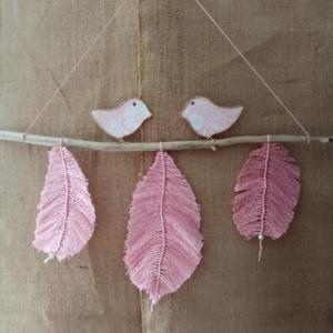 Suspension de trois plumes en macramé avec deux petits oiseaux en fil de kraft armé, posés délicatement sur une branche de bois flotté