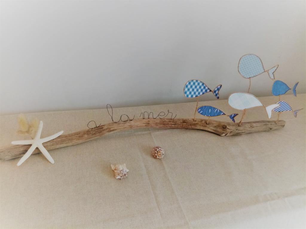 Décoration sur le thème de mer avec poissons en fil de kraft arme couleur bleue posés délicatement sur une branche de bois flotté. Une étoile de mer est collée à l'extrémité du bois.