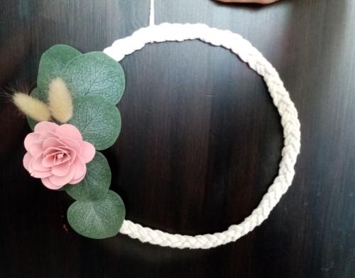 Couronne de macramé tressé avec fleur en bois de couleur rose et des petites feuilles d'eucalyptus.