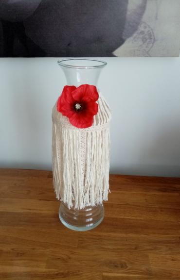 Vase bouteille entouré de macramé et agrémenté d'une fleur de coquelicot