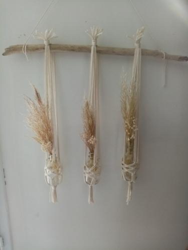Trois soliflores en macramé suspendus sur une branche de bois flotté. Des fleurs de pampa et du gypsophile séché agrémentent ces soliflores