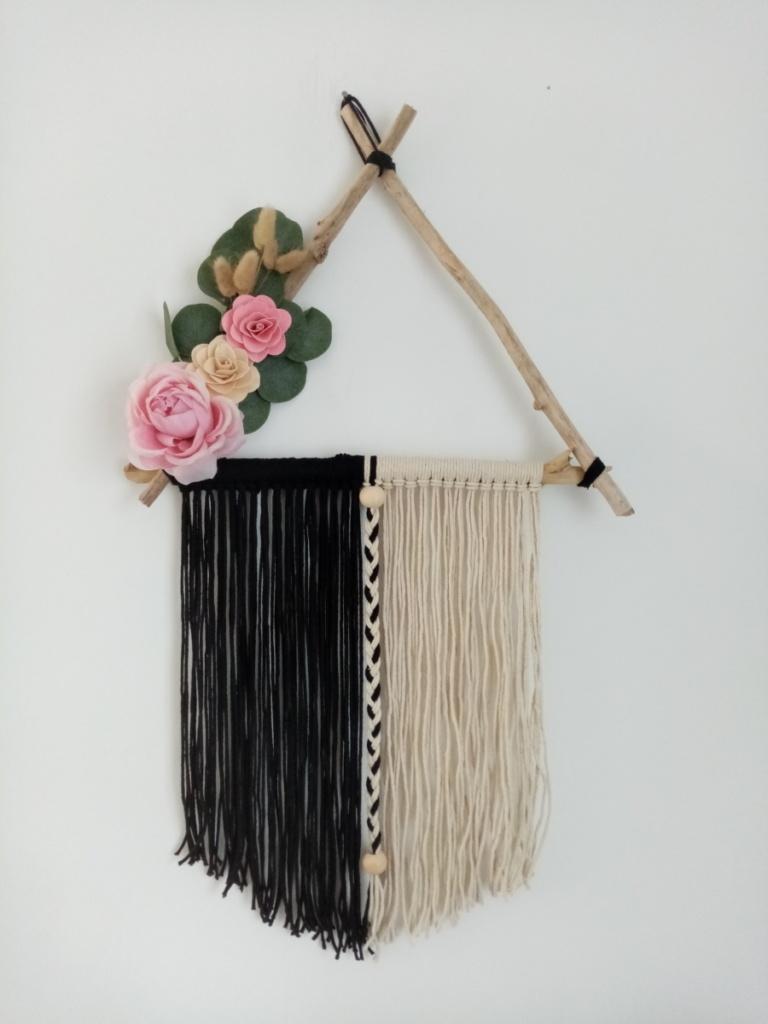 Suspension en macramé noir et blanc tenu par des branches de bois flotté placés en triangle, agrémentée de fleurs en bois, en tissus et d'eucalyptus.