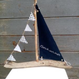 Bateau en bois flotté avec une voile bleu marine et une inscription berck sur mer en broderie fait main ainsi qu'une guirlande de petits fanions tissus blanc et petits pois bleus