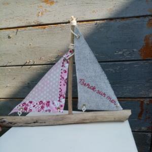 Bateau en bois flotté avec deux voiles. Une voile gris chiné et une autre voile rose fleurie