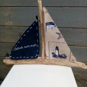 """Bateau en bois flotté avec deux voiles. Une voile tissus bleu marine avec inscription en broderie blanche """" Berck sur mer"""" et une autre voile couleur crème et des imprimés bleu marine"""