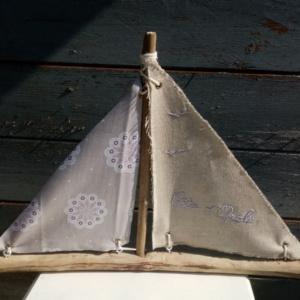 Bateau en bois flotté avec deux voiles en tissus. Une voile en lin et une voile tissus gris fleuri et rose
