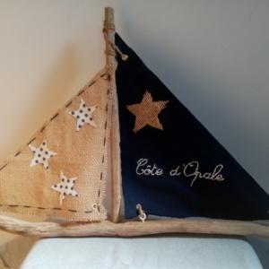 """Bateau en bois flotté avec deux voiles. Une voile en tissus bleu marine avec inscription """" Côte d'Opale' en broderie rose clair et une autre voile en toile de jute avec des étoiles de tissus blanc à petits pois blanc."""
