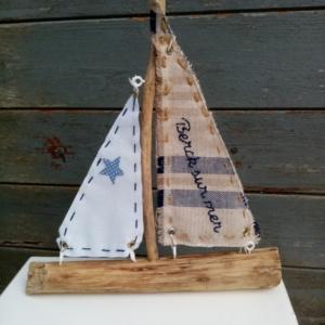 """bateau en bois flotté avec deux voiles. Une voile en tissus bleu et crème avec inscription """" Berck sur mer"""" en broderie bleu marine et une autre voile tissus blanc."""