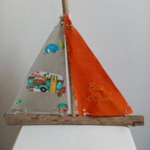 """Bateau en bois flotté avec deux voiles. Une voile couleur orange et une inscription """" Côte d'Opale"""" en broderie jaune et une autre voile avec des imprimés combi."""