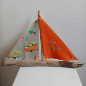 """Bateau en bois flotté avec deux voiles. Une voile couleur orange et une inscription """" Côte d'Opale"""" en broderie bleu clair et une autre voile avec des imprimés de caravanes vintage."""