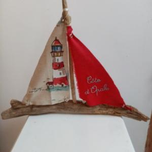 """Bateau en bois flotté avec deux voiles. Une voile rouge et une inscription """" Côte d'Opale"""" en broderie bleu clair et une autre voile avec un imprime d'un phare."""