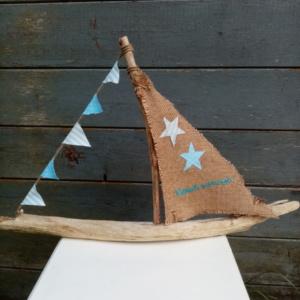 """Bateau en bois flotté avec une voile en toile de jute et inscription """" Berck sur mer"""" en broderie bleu clair et une banderole de tissus bleu ciel à petits pois blanc et tissus rayé ."""