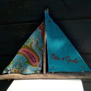 """Bateau en bois flotté avec deux voiles. Une voile tissus bleu avec inscription orangé """"Côte d'opale"""" et un tissus couleur cachemire."""