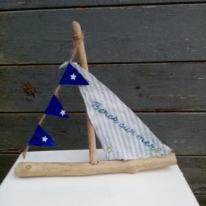 """Petit bateau en bois flotté avec une voile blanche et rayure gris clair avec une inscription """" berck sur mer"""" en broderie bleu et une banderole avec tissus bleu marine"""