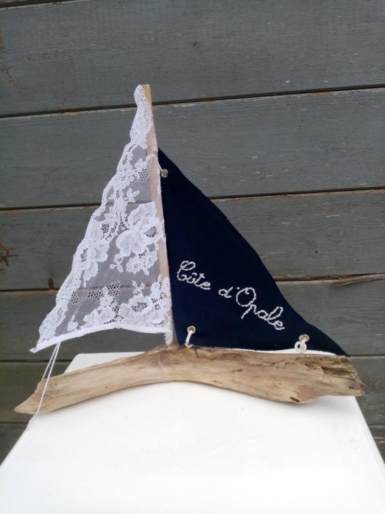"""petit bateau en bois flotté avec deux voiles. Une voile en tissus bleu marine avec inscription """" Côte d'opale"""" en broderie blanche et une autre voile en véritable dentelle de Calais."""
